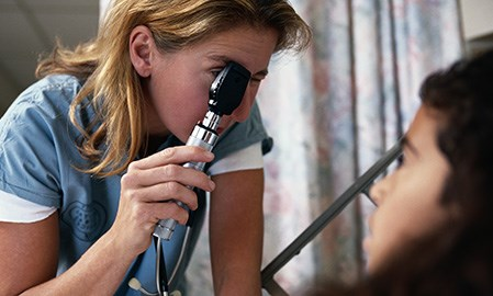 A clinician administers an eye exam. (credit: PhotoDisc)